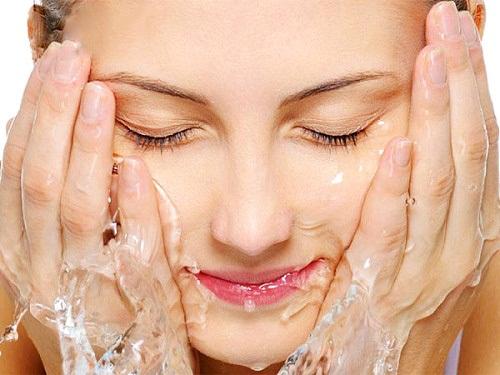 Cách làm sữa rửa mặt tự nhiên cho từng loại da - hình phụ nữ rửa mặt bằng nước khoáng